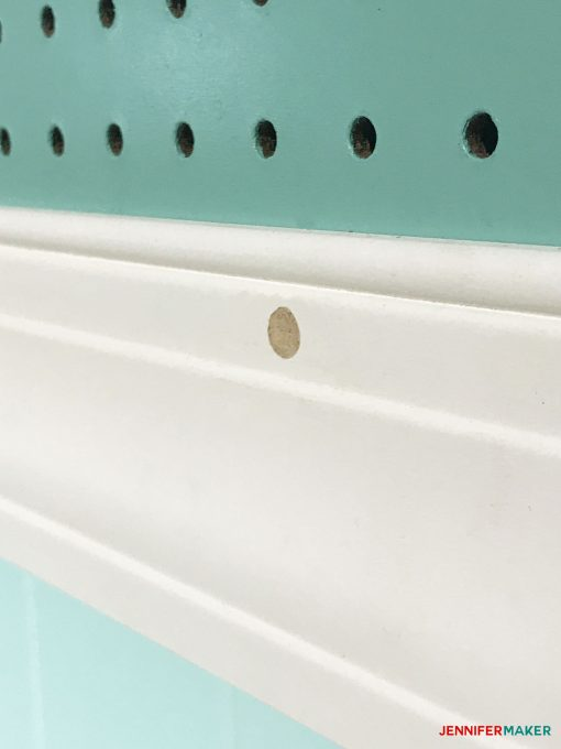Spackling over the screw heads on our large framed pegboard