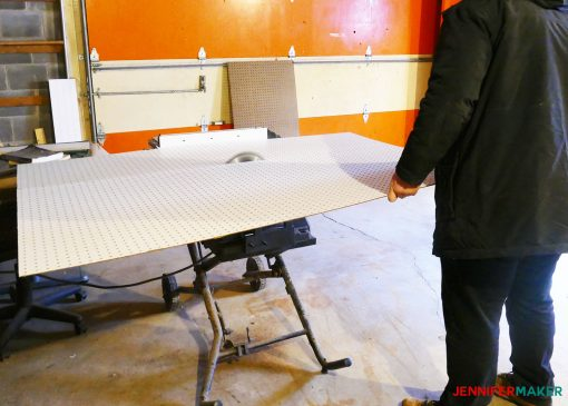 Cutting our large sheet of pegboard on a table saw