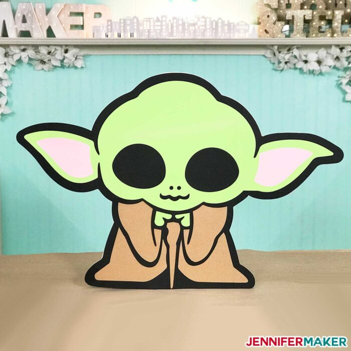 Larger than mat cardstock cutout of baby yoda in Jennifer's craft room - made on a Cricut!