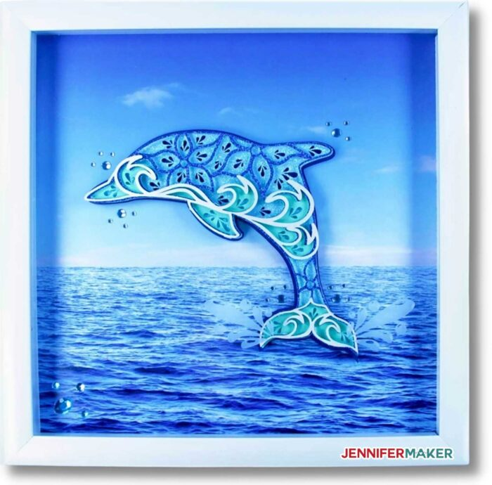 Layered Dolphin Mandala in blue cardstock with rhinestone droplets, framed in a white shadow box