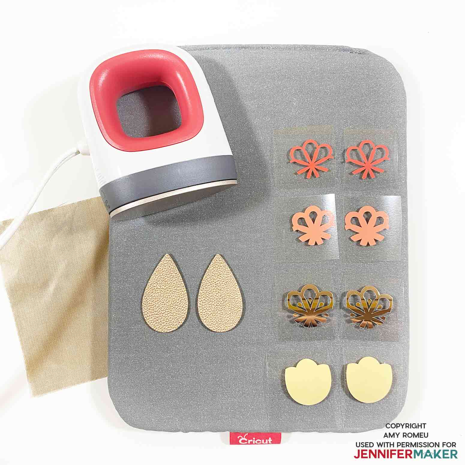 Cricut easy press mini and vinyl earring shapes on a pressing pad