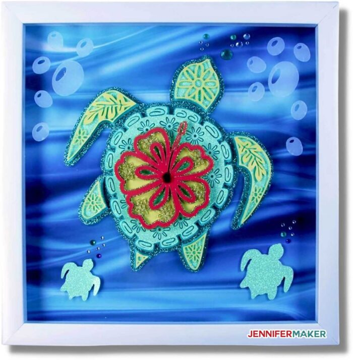 Layered Turtle Mandala in green and blue cardstock with vinyl accents, framed in a white shadow box