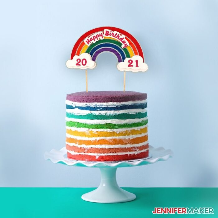A bright rainbow layer cake  with a Cricut cake topper with layers