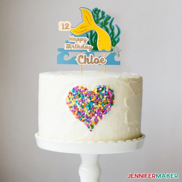 A white cake with a cardstock mermaid cake topper with fun layers made on a Cricut cutting machine