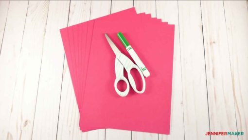 Pink paper and scissors, ready to cut and make giant paper flowers