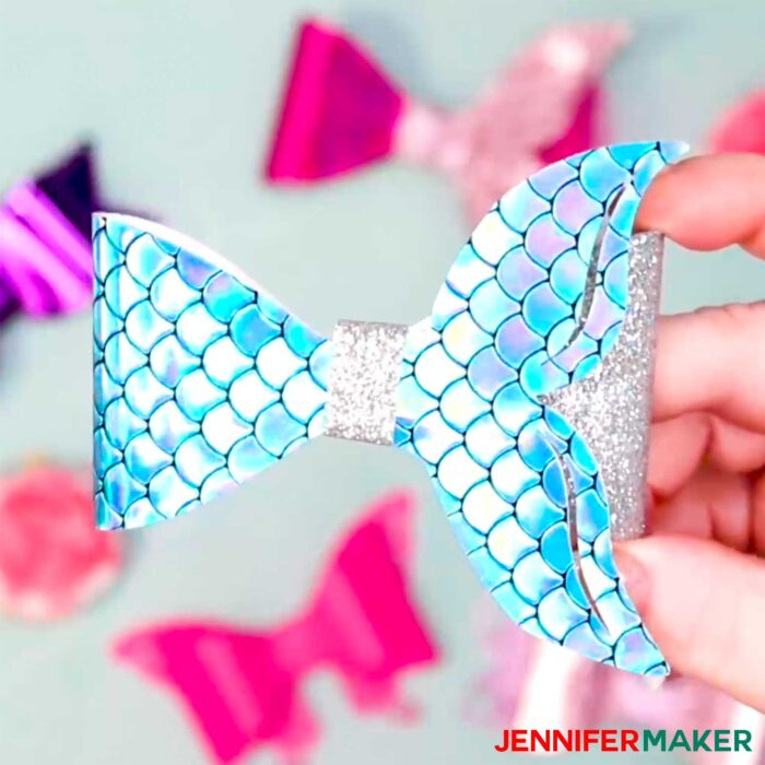 A turquoise blue mermaid tail hair bow made with faux leather and cut on a Cricut Maker