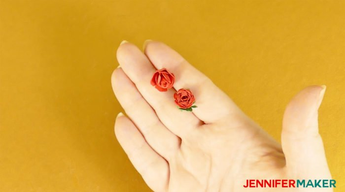 Two miniature paper roses made from red cardstock in a hand