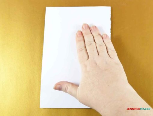 Pressing down on the folded pop-up heart card
