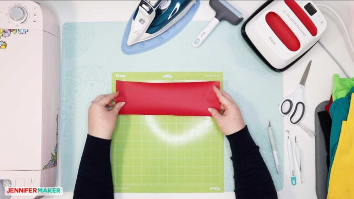 Place a red piece of iron on vinyl shiny side down on a green Cricut StandardGrip cutting mat to cut out an iron on design for a T-Shirt