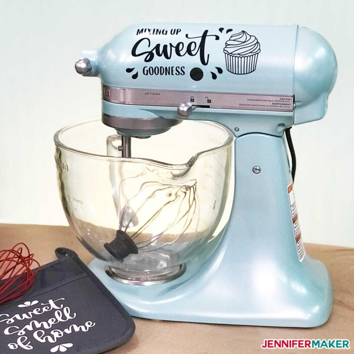 "Blue KitchenAid stand mixer with vinyl decal on it that reads, ""Mixing Sweet Goodness"""