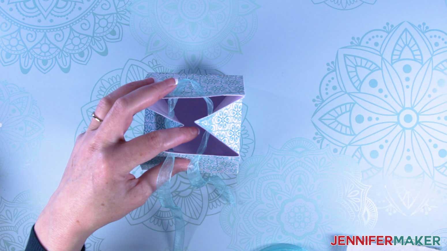 Thread ribbon through the holes of the milk carton mug gift boxes