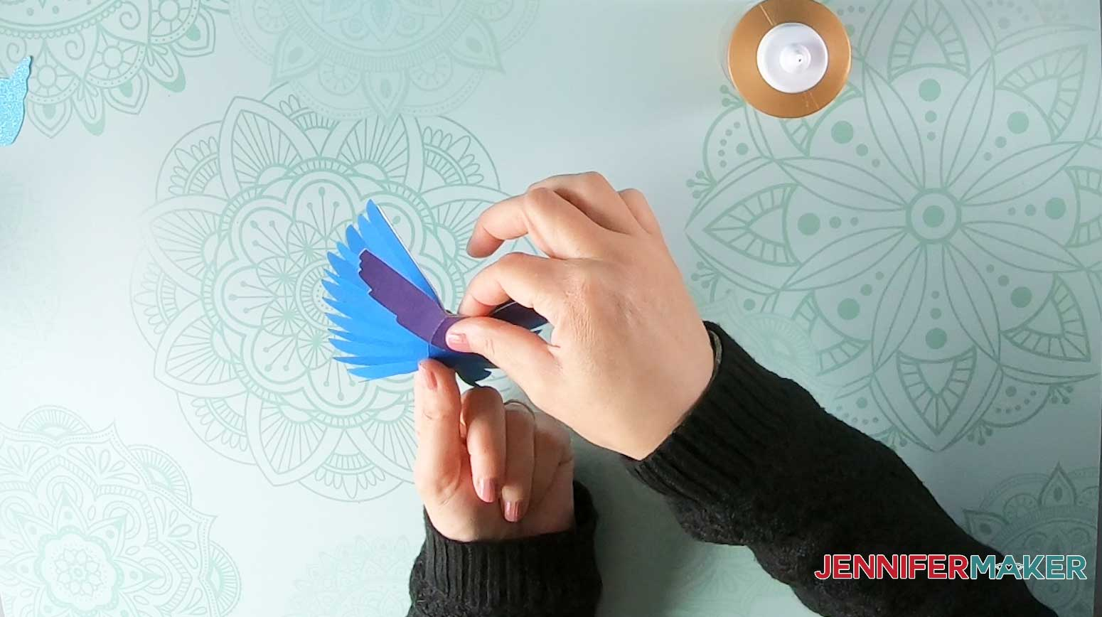 Glue the paper bird bottom decorative accent piece onto the underside of the wing