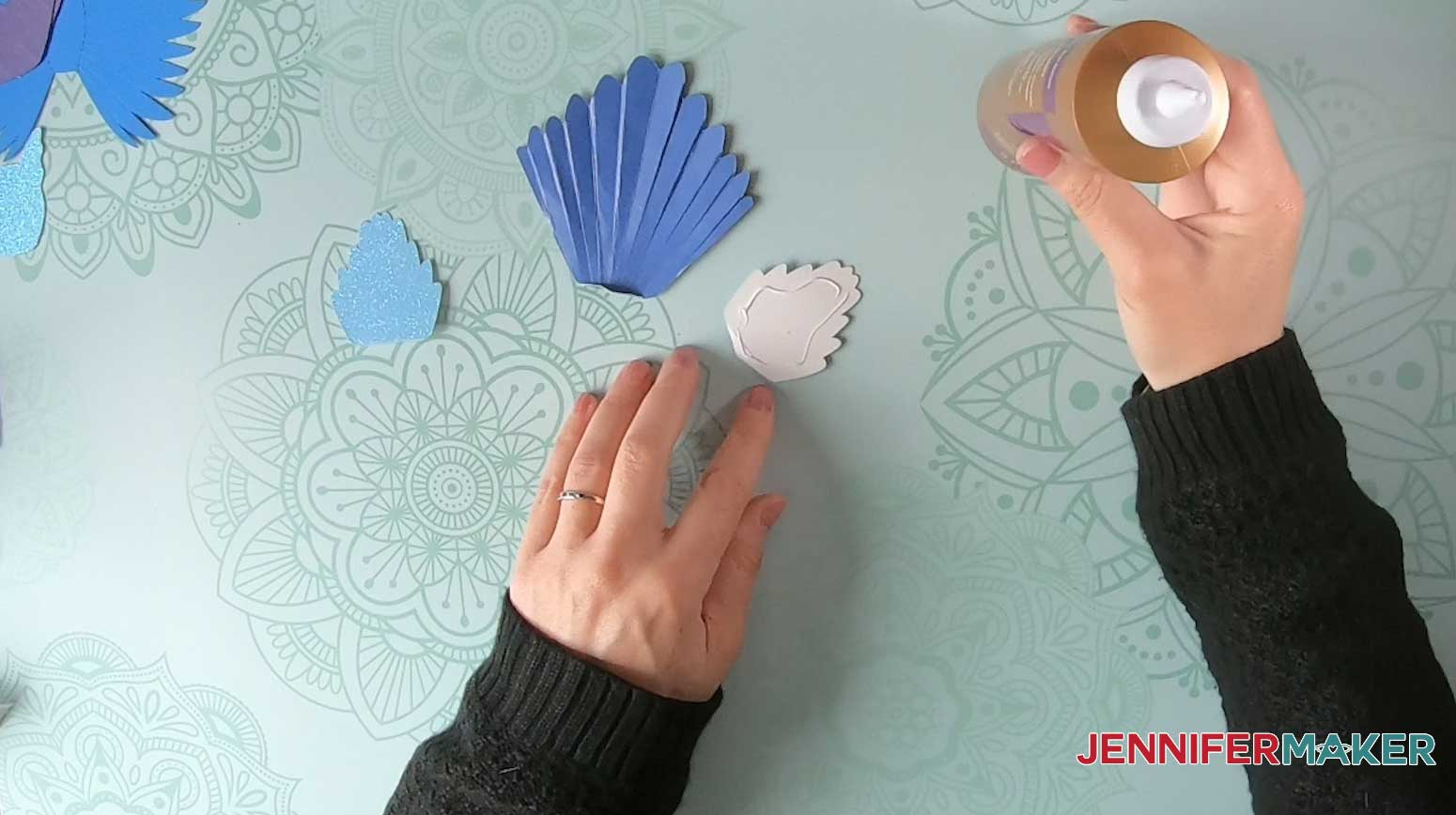 Glue the paper bird decorative pieces to the tail