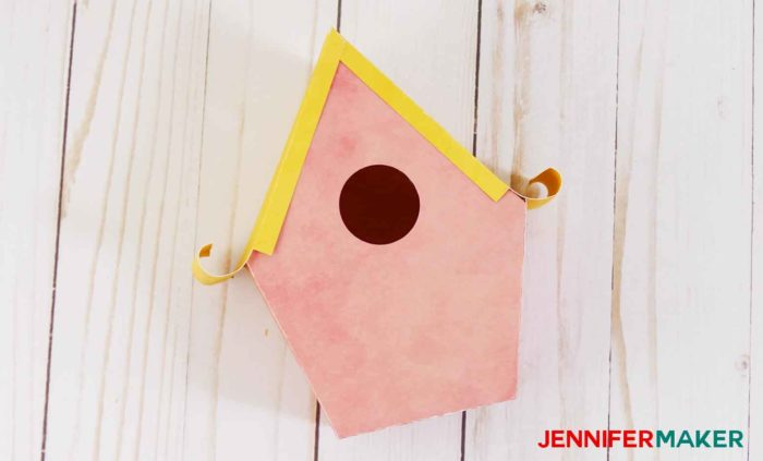A finished pink paper birdhouse with a yellow rolled edge roof