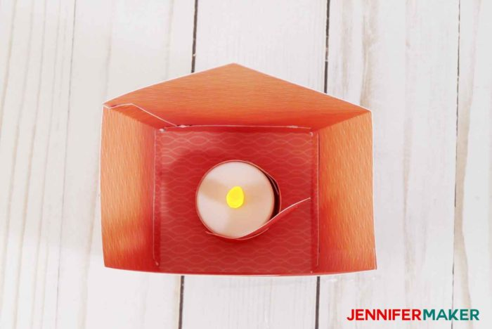 Place the LED tealight with the paper bird inside your paper birdhouse
