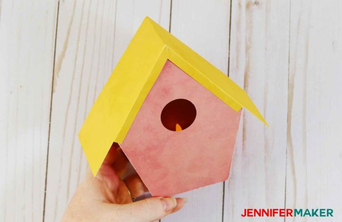 A yellow paper roof on a pink paper birdhouse