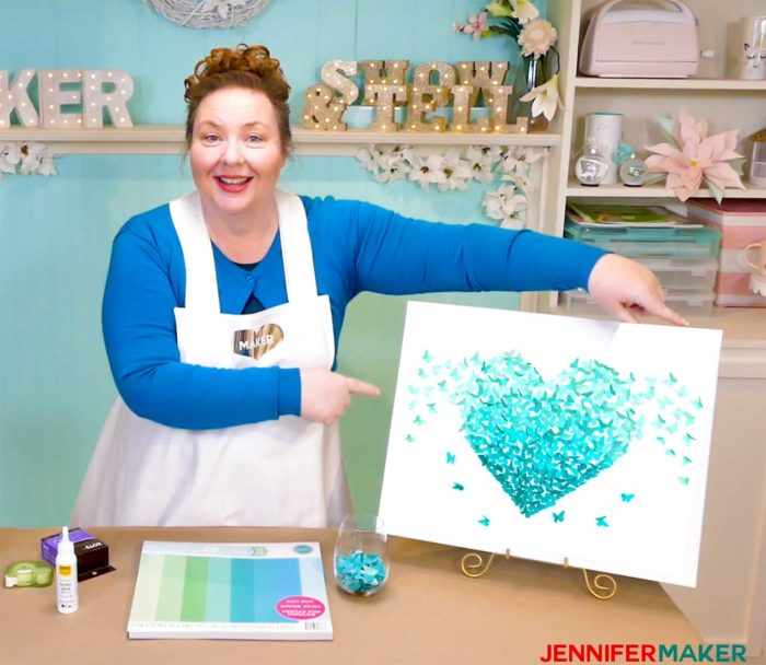 Jennifer Maker points to her blue paper butterfly canvas of a winged heart