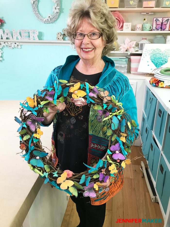 My mom holding her pretty paper butterfly wreath made with the Print Then Cut feature on the Cricut!