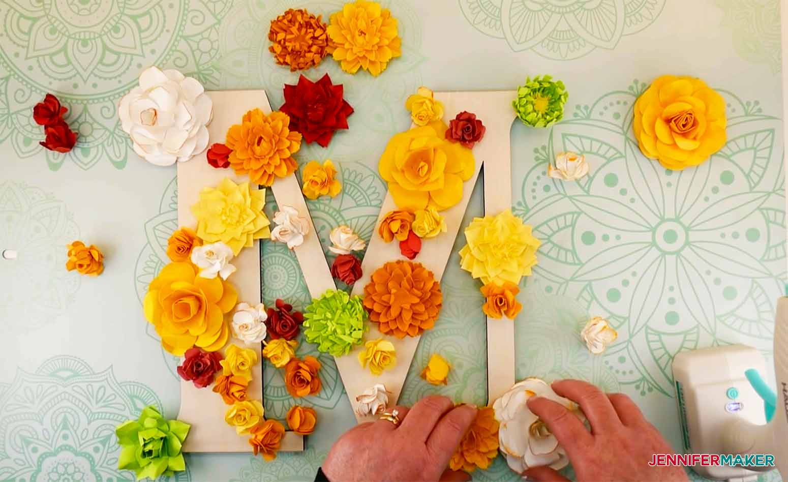 Ready to glue flowers in place on paper flower letter.