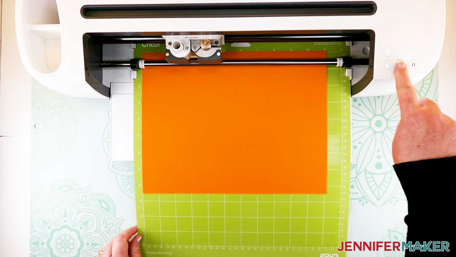 pressing start button on cricut machine for paper flower letter project