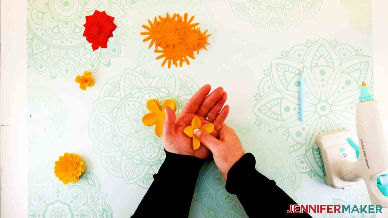 pushing petals into palm of a paper flower letter