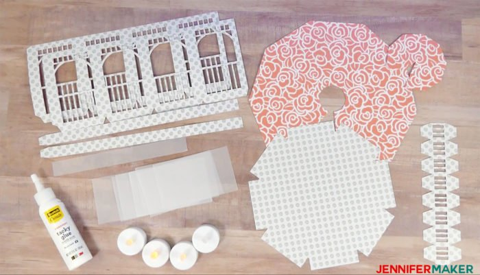 Materials to make a paper gazebo luminary with cardstock, vellum, LED lights, and tacky glue