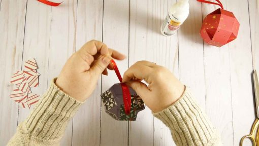 Push the ribbon through the hole in the tabs at the top of your paper orb