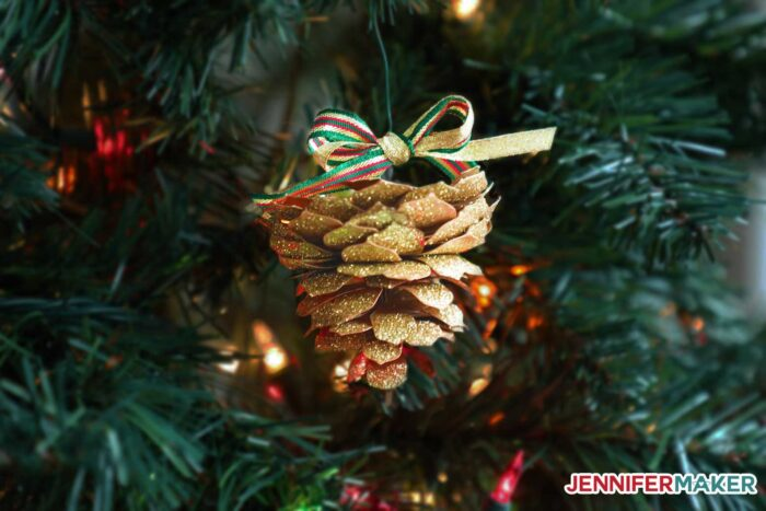 A paper pine cone hanging from a Christmas tree