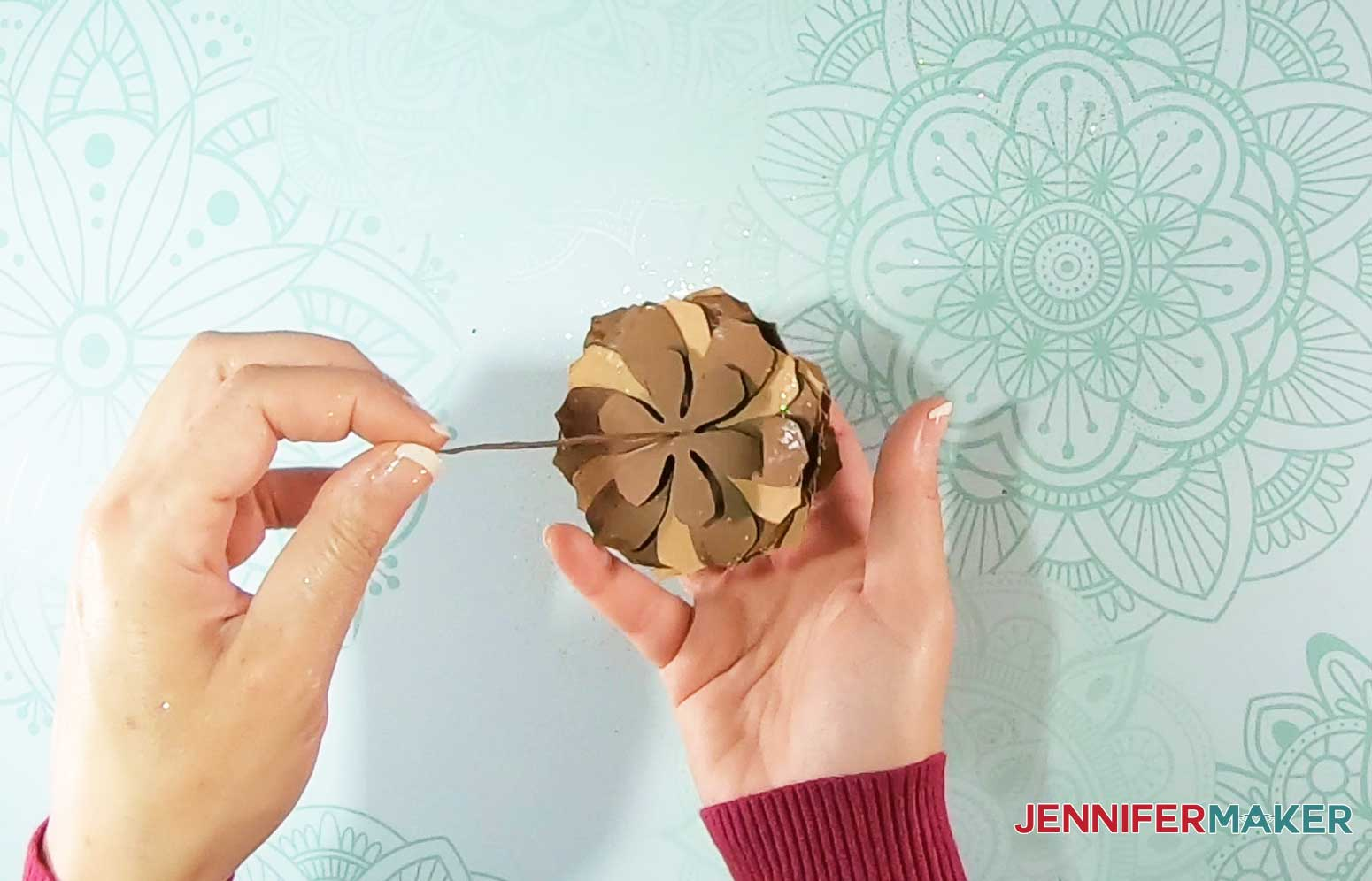 Thread paper pinecone base onto stem
