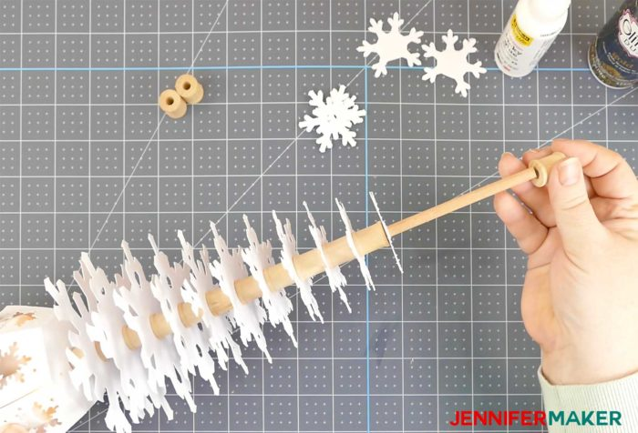A wooden dowel filled with paper snowflakes and spools to create a paper snowflake Christmas tree