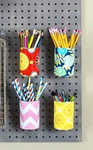 Make your own hanging cups from aluminum cans for your pegboard! You NEED a pegboard in your craft room! This is the ultimate guide to pegboards, filled with #organization ideas, #storage tricks, and craft room decor tips. #craftroom #diydecor