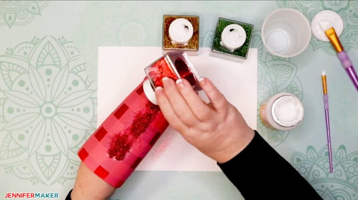 Applying red glitter to a painted and taped tumbler to make a plaid glitter tumbler