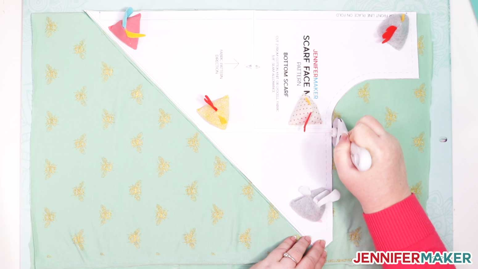 Cutting out green fabric using a rotary blade and DIY pattern weights