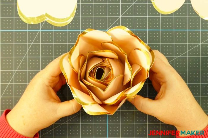 Pink paper with gold foil edges shaped into a big bud for a rose gold paper flower