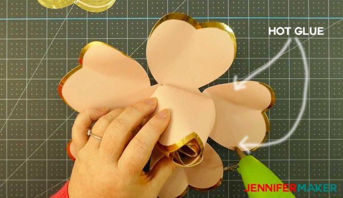 Gluing the paper petals onto a giant rose gold paper flower