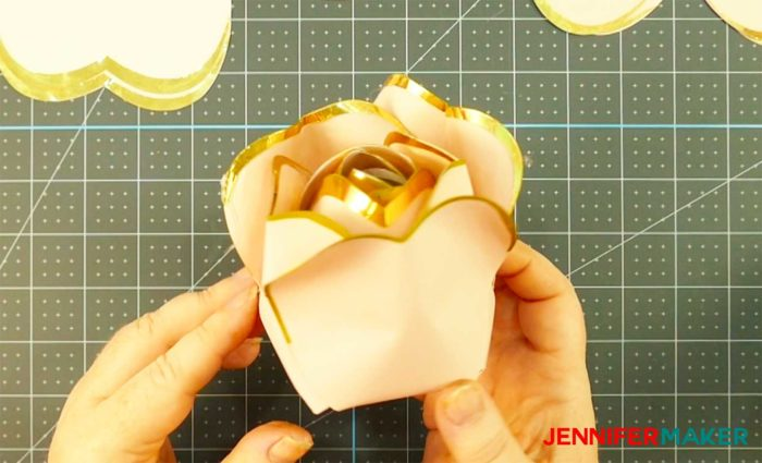 Pink paper with gold foil edges formed into a bud to make a giant rose gold paper flower