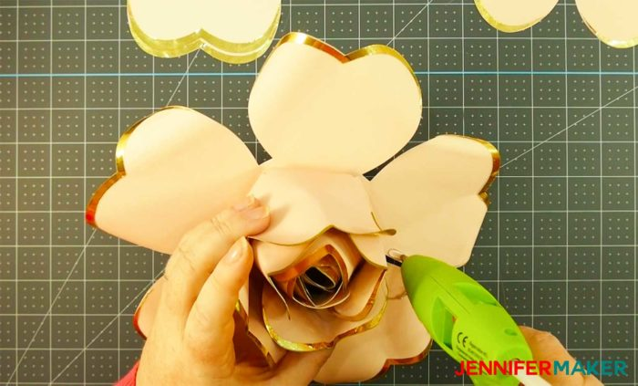 Putting hot glue on paper rose petals to make a giant rose gold paper flower