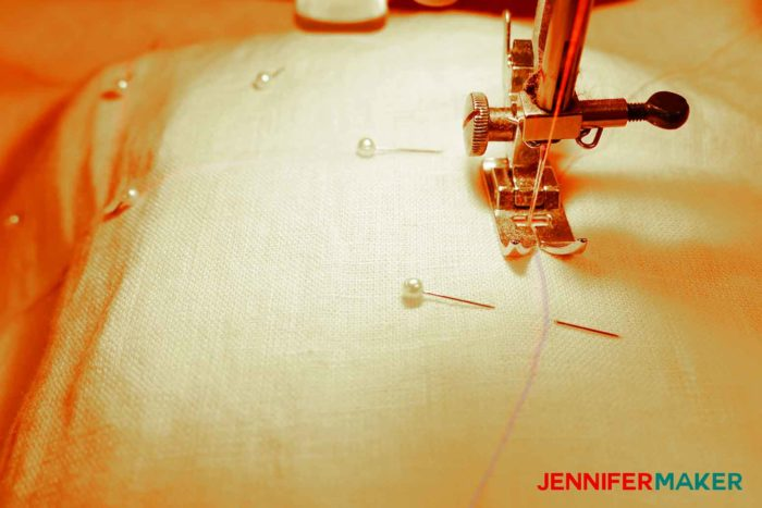 Sewing the facing to the garment to sew a round jewel neckline on a shirt or tunic