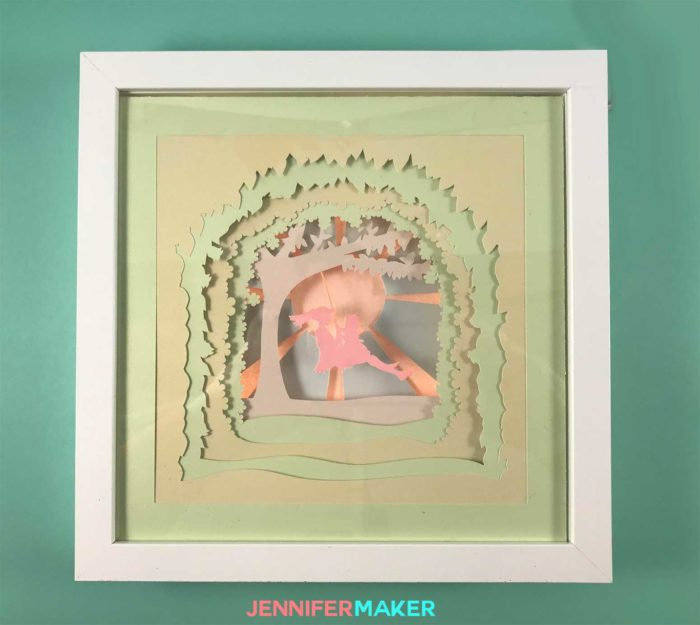 A lighted shadow box paper art template of a mother and daughter on a tree swing - made with pastel cardstock