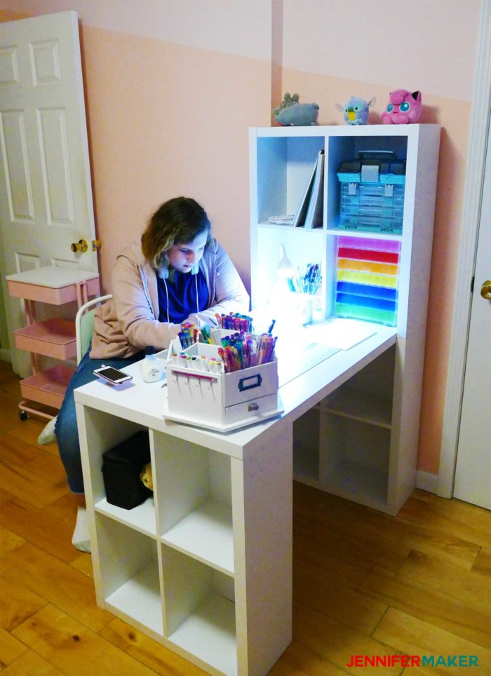 A teen girl sits at a white craft table in a pink room -- this is an affordable craft table