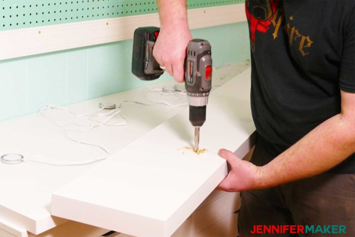 Drilling the hole into the shelf to install under shelf lighting cheap and easy