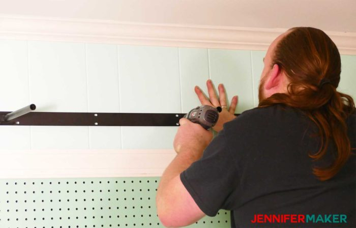 Attaching the floating shelf bracket hardware to the wall with a cordless drill - how to install under shelf lighting cheap and easy