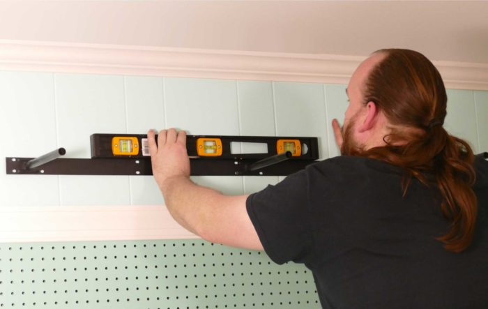 Checking that the floating shelf bracket is level as we install under shelf lighting cheap and easy
