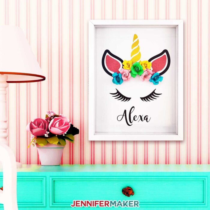 Make a paper flower unicorn shadow box and personalize it with a name using vinyl and cardstock!