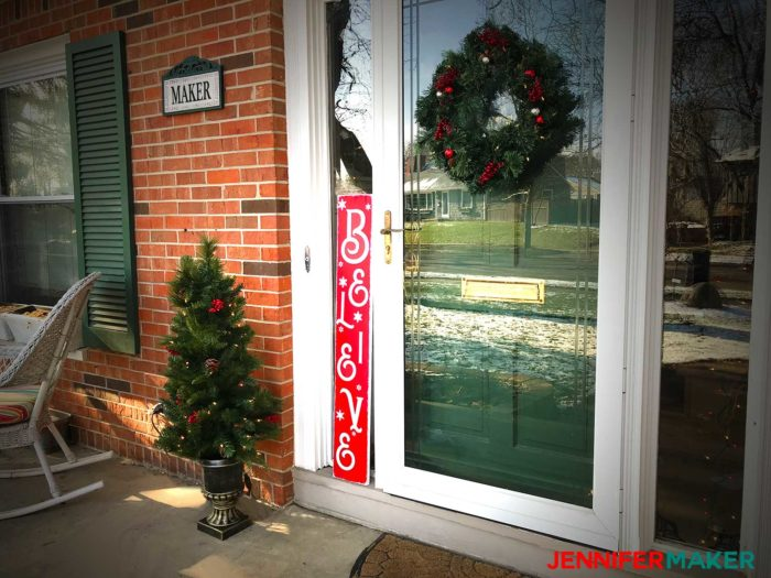 "A vertical red ""Believe"" holiday sign on a front porch for Christmas"