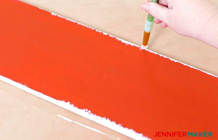 Creating a snowy look with white paint on a red board to create a vertical holiday sign