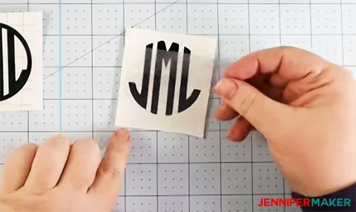 Applying transfer tape to a black vinyl decal for a mug
