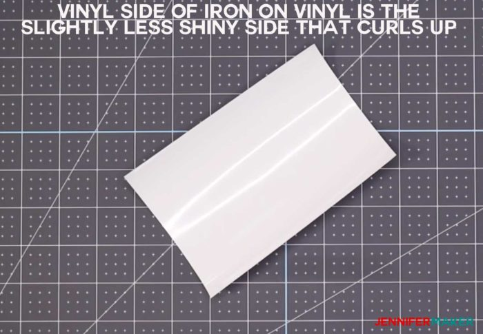 A piece of white iron-on vinyl showing the less shiny vinyl side which is the side you put up on your cutting mat