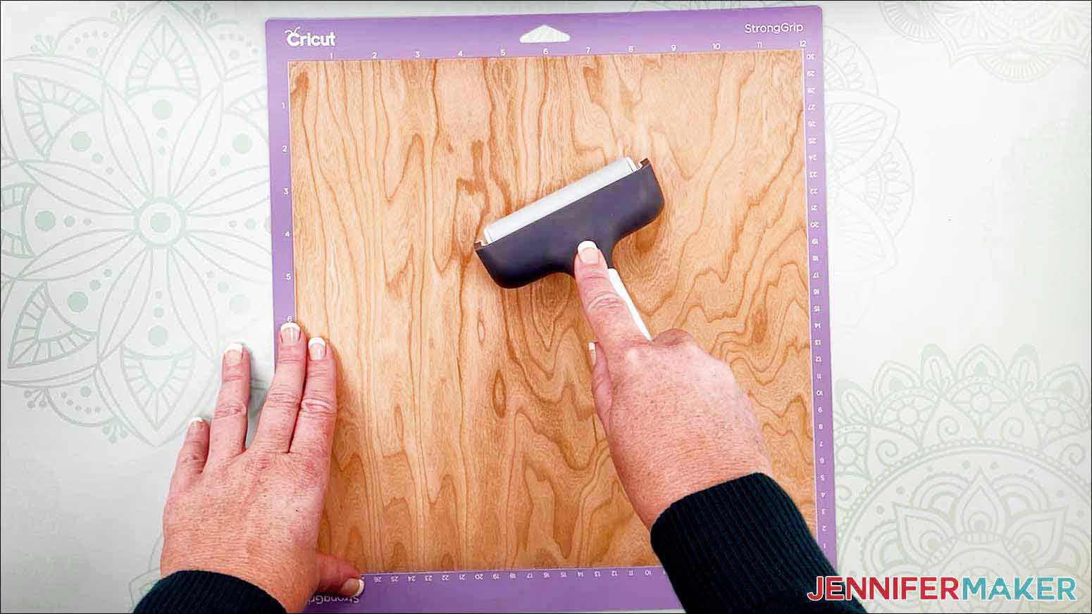 Use a brayer to flatten the veneer to the machine mat for my wooden bookmarks project