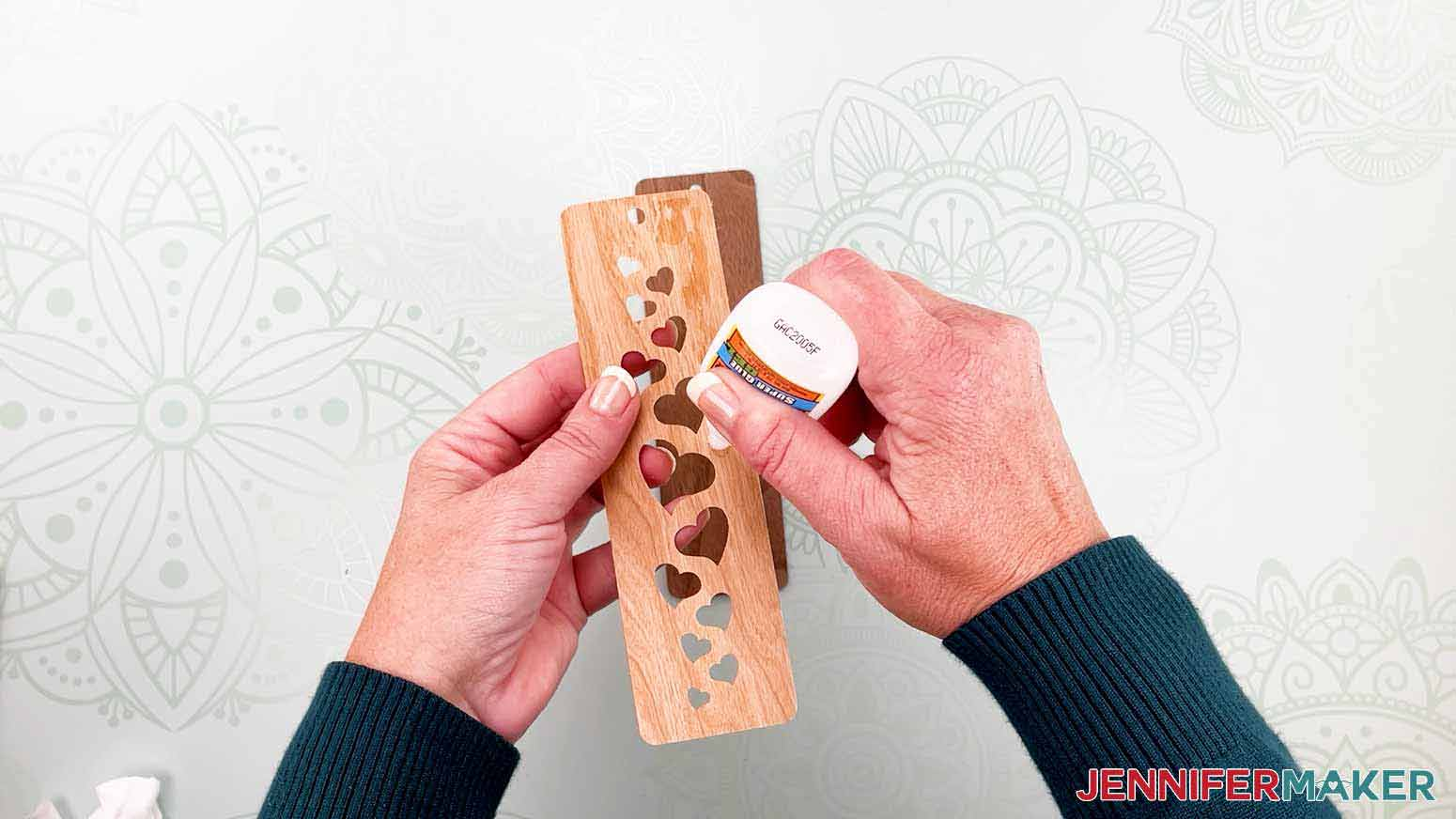 Add glue to the back of the bookmark design for my wooden bookmarks project